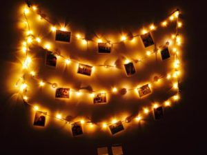 LED lights hanging on a bedroom wall with pictures of friends